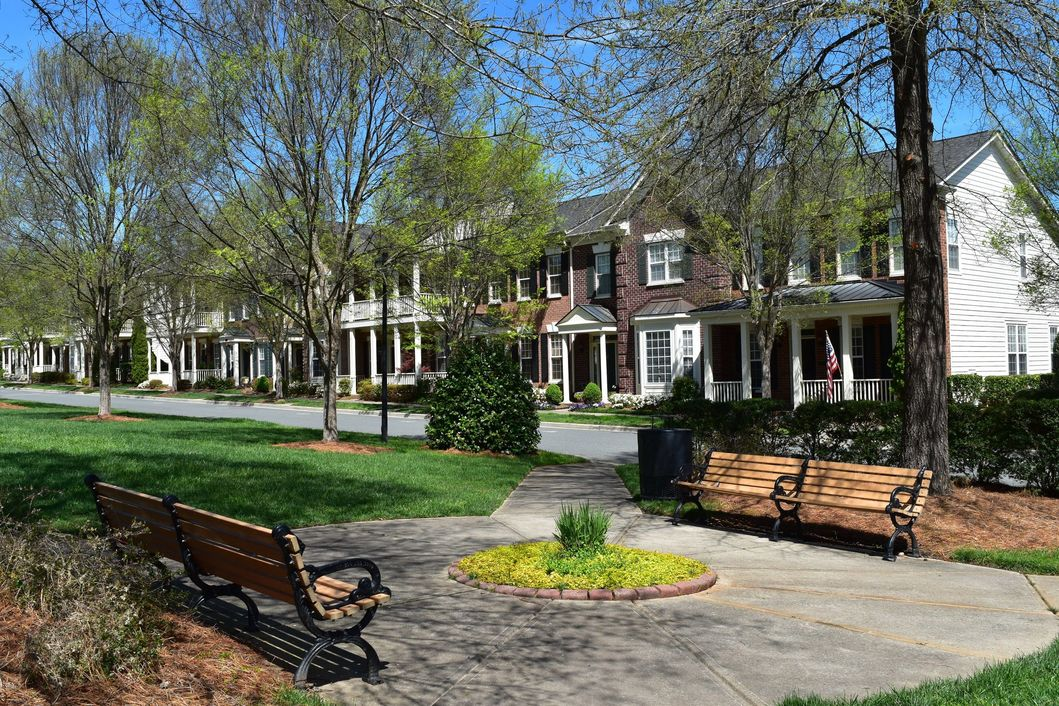 Old Davidson Townhomes and park benches on the green.