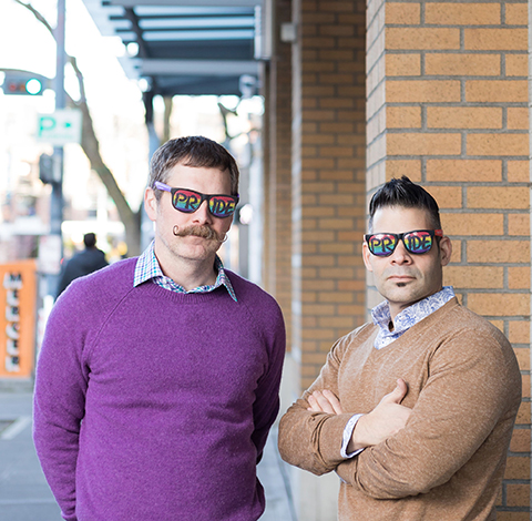 Picture of Erik and Joe outside on sidewalk. They are wearing rainbow glasses and being serious