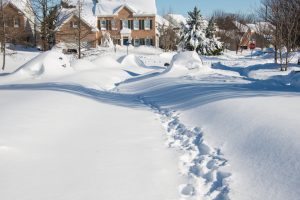 The street of a suburb neighborhood in Northern Virginia is covered with over two feet of snow after a recent blizzard. There is a trail in the snow down the middle of the street. It will be a while before cars will be able to drive down the street.