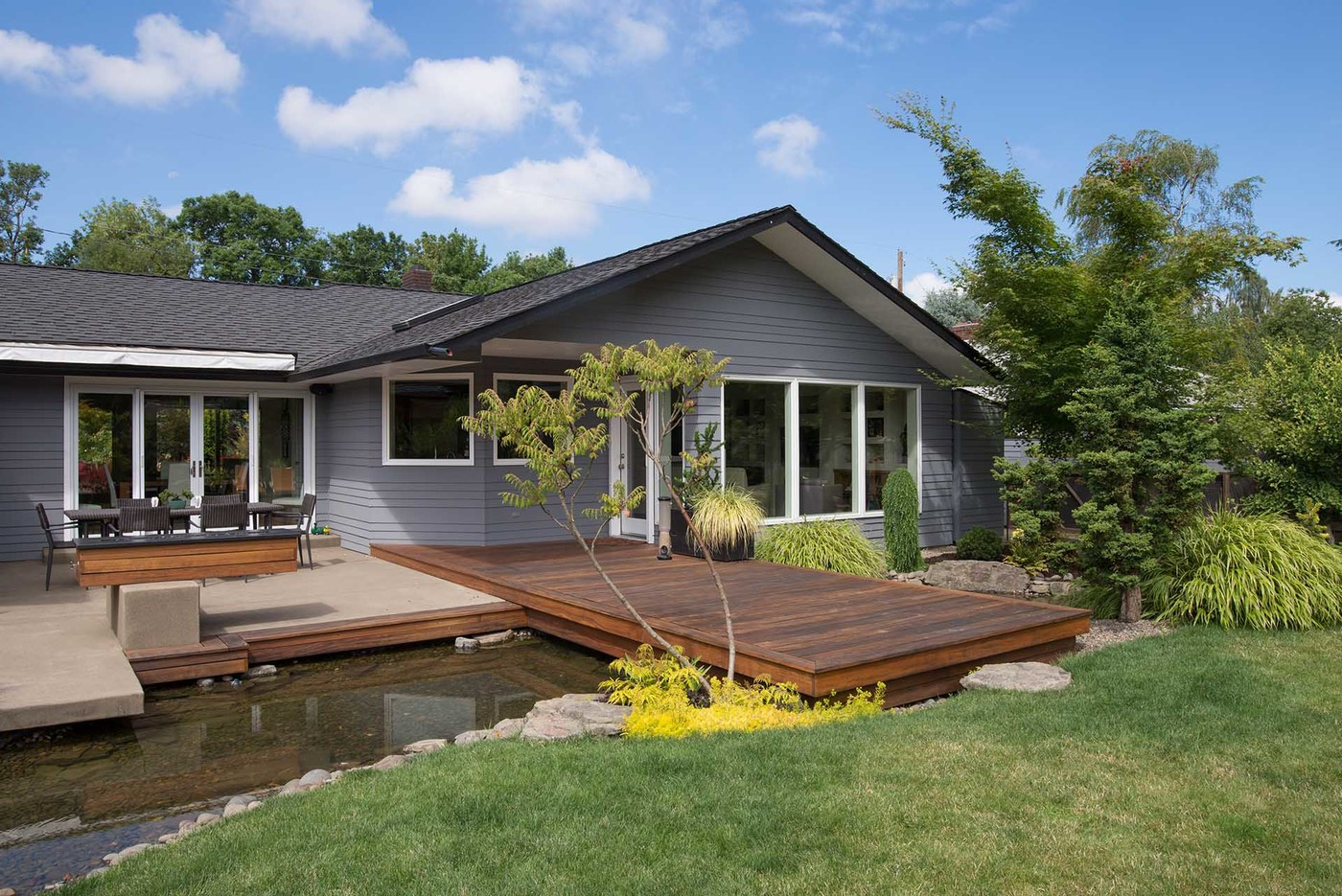 A blue summer sky punctuated with fluffy white clouds serves as the perfect background for this portrait of a contemporary Pacific Northwest home featuring a deck that spans a water feature emulating a rock lined stream that enhances their backyard.