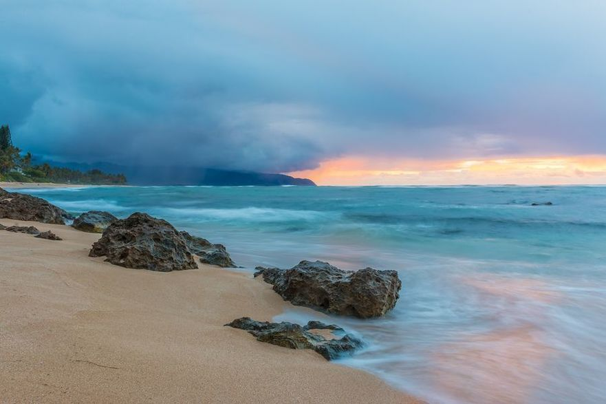 Skies on fire at sunset with the rain in the background in North Shore Oahu Hawaii
