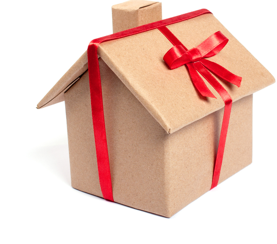 House as a gift. A gift wrapped in kraft paper in the form of a house and tied with a red ribbon. Isolated on white background
