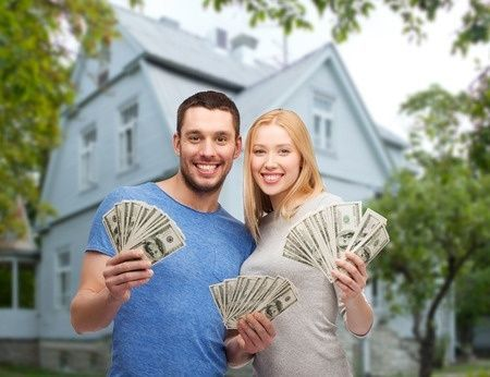 36052422 - love, people, real estate, home and family concept - smiling couple showing dollar cash money over house background
