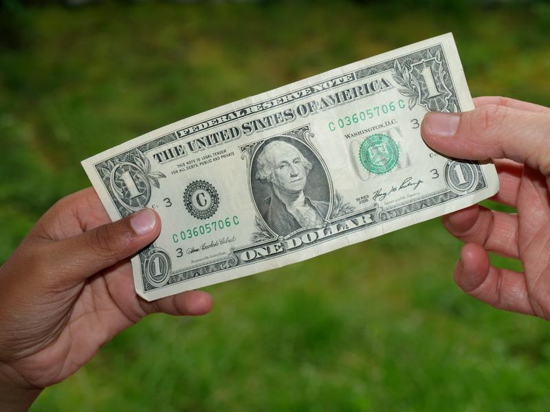 bigstock-giving-dollar-bill-5601875