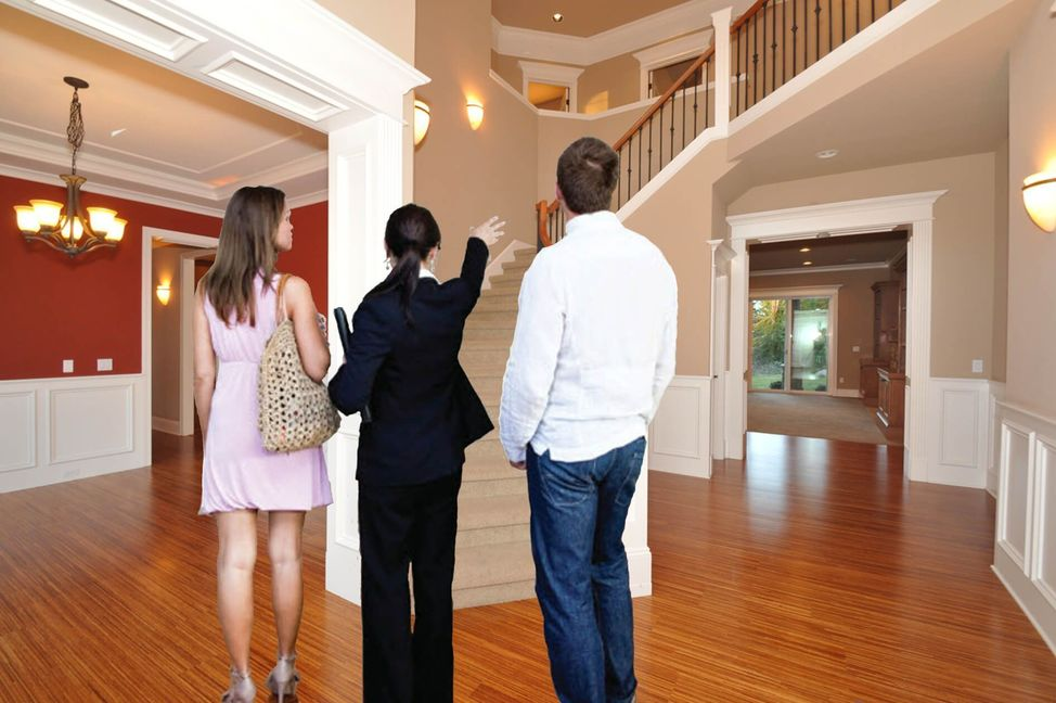 Real Estate Agent showing a home to Clients standing in the foyer