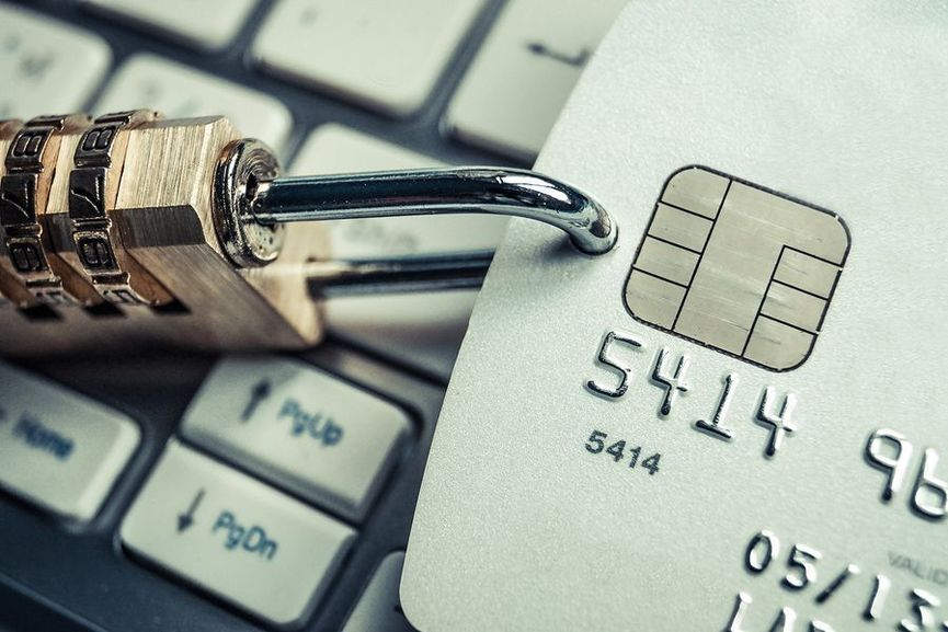 a security lock with password with a credit card on white computer keyboard representing credit card data encryption for financial security