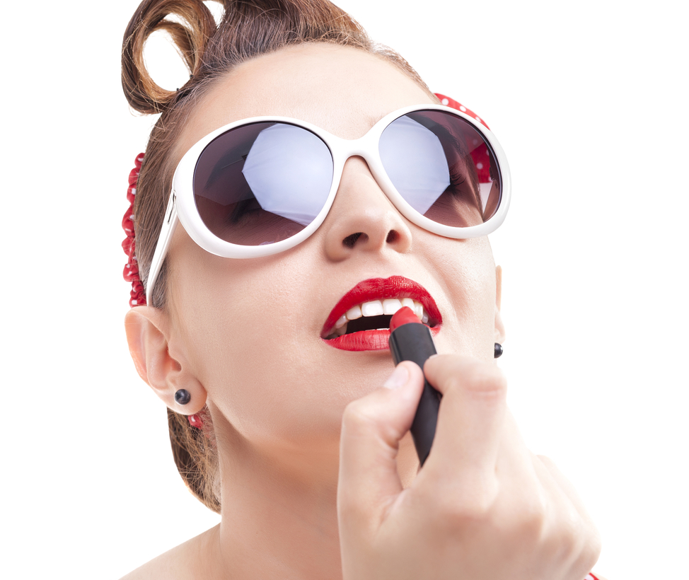 Pin-up gir in sunglasses applying red lipstick on the lips, isolated over white background