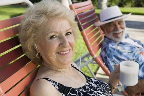 Senior Couple sitting on lawn chairs, woman listening to earphones and holding cup, portrait.