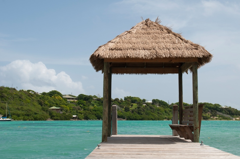tropical wooden jetty with hut over sea in Long Bay, Antigua