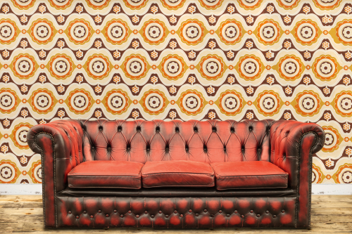 Retro styled image of an old sofa against a vintage wallpaper wall