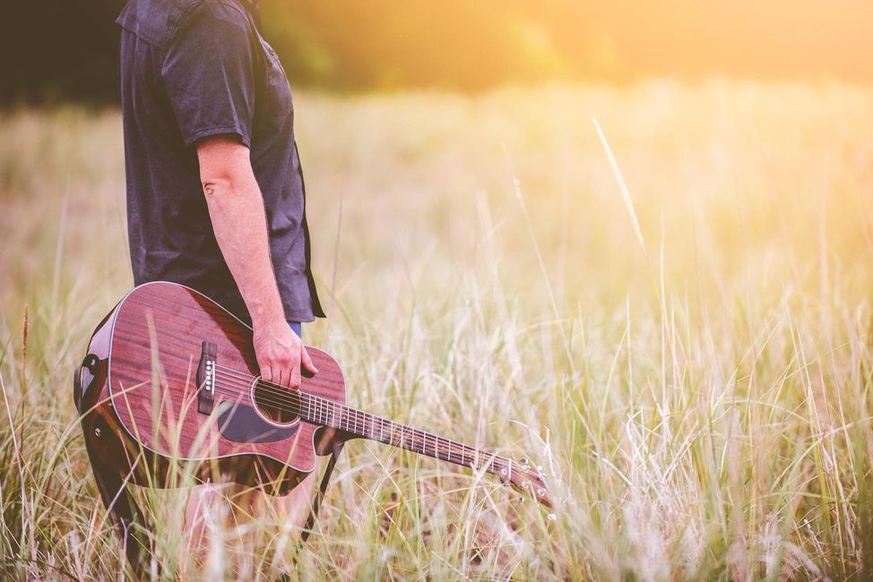 man-in-field-with-guitar