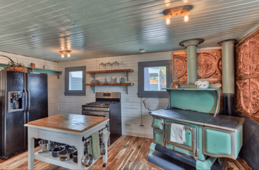 Kitchen with fridge, island, range, and antique teal stove