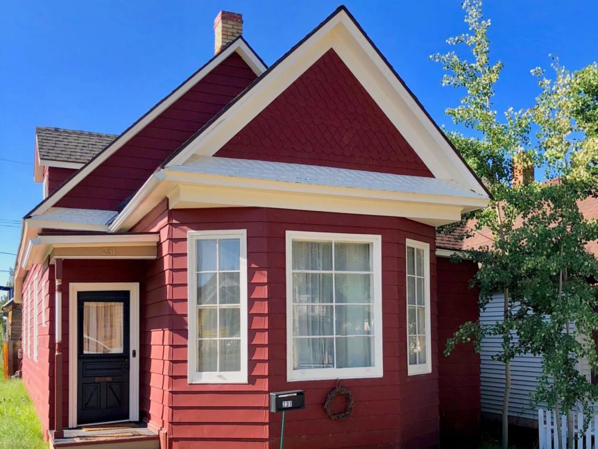 Front of Victorian home with red siding and big windows