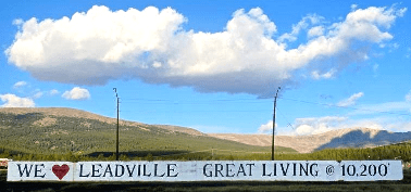"Clouds above and rolling hills behind a white sign that reads ""We [heart] Leadville - Great Living @ 10,200'"""